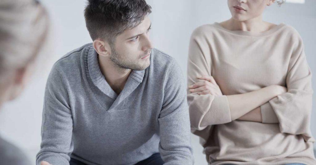 Mand med udslåede arme til en terapi session for par